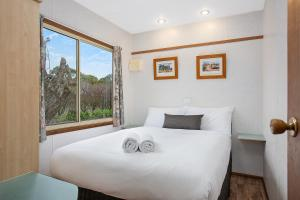 A bed or beds in a room at Lake Hamilton Motor Village and Caravan Park