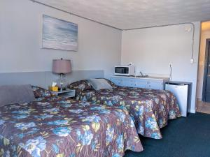 A bed or beds in a room at Skyline Motel