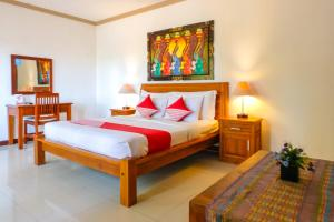 A bed or beds in a room at OYO 954 Family House Lombok Hotel