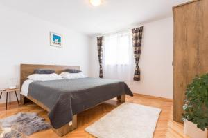 A bed or beds in a room at Apartments Lidija - see view with private hot tub and split level apartment with garden