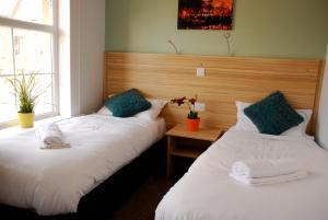A bed or beds in a room at Botanic Rest Queens Quarter