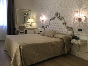 A bed or beds in a room at Hotel Gorizia a La Valigia