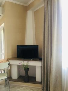 Телевизор и/или развлекательный центр в Квартира У моря, с видом на горы