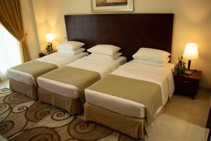 سرير أو أسرّة في غرفة في روز جاردن للشقق الفندقية - البرشاء