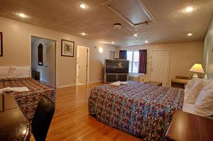A bed or beds in a room at Economy Motel Inn and Suites Somers Point