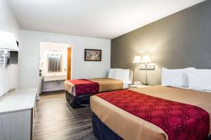 A bed or beds in a room at Econo Lodge Airport I-35 North