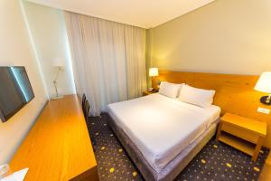 A bed or beds in a room at Hotel Agimi