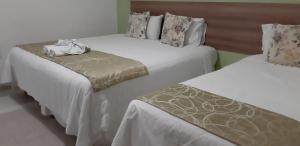 A bed or beds in a room at Hotel Cantinho Verde