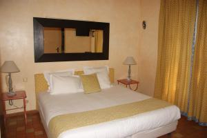 A bed or beds in a room at Auberge des Glycines