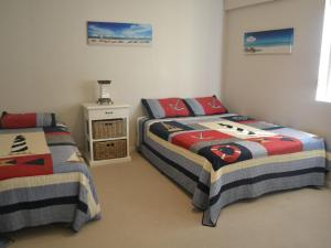 A bed or beds in a room at Beachside 4 with Airconditioning and Spa Bath