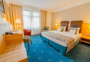 A bed or beds in a room at Greno Hotel & Spa