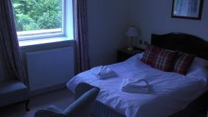 A bed or beds in a room at Kirroughtree Manor House