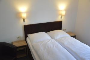 A bed or beds in a room at Gästehaus/Pension Fässle