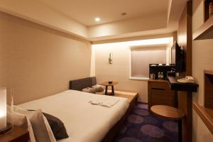 A bed or beds in a room at Hotel Ryumeikan Tokyo
