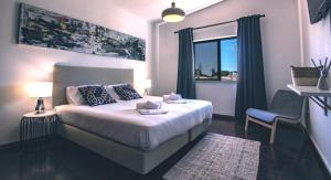 A bed or beds in a room at Pine House - Faro Airport, Beach and City Center