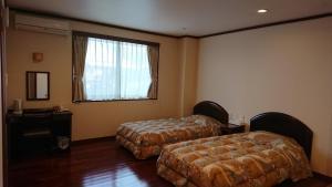 A bed or beds in a room at Jomon no Yado Manten