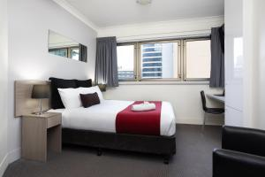 A bed or beds in a room at George Williams Hotel