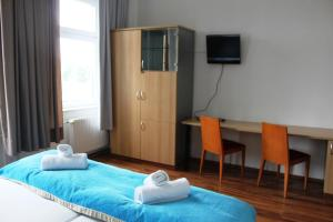 A bed or beds in a room at Elbe's Hotel Dresden