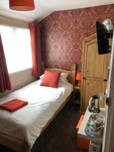 A bed or beds in a room at Willows Guest House