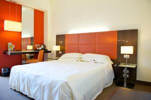 A bed or beds in a room at Mercure Reggio Emilia Centro Astoria