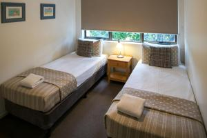 A bed or beds in a room at Noosa Shores Resort