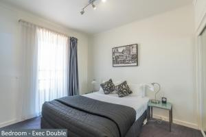 A bed or beds in a room at Clocktower Apartment Hotel