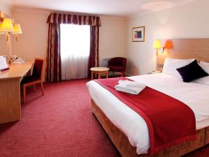 A bed or beds in a room at Mercure Chester North Woodhey House Hotel