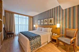A bed or beds in a room at Hotel Brasil 21 Suites