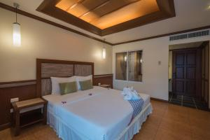 A bed or beds in a room at Mac Resort Hotel