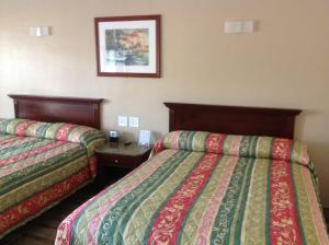A bed or beds in a room at Sunshine Inn of Daytona Beach
