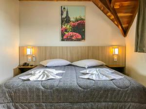 A bed or beds in a room at Hotel Gramado Garden
