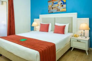 A bed or beds in a room at Queen's Park Goynuk Hotel - All Inclusive