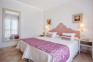 A bed or beds in a room at Grupotel Macarella Suites & Spa