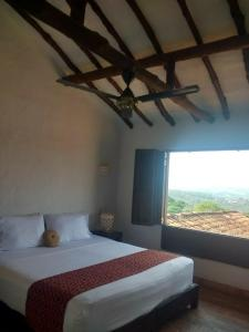 A bed or beds in a room at La Loma Hotel Barichara