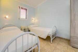 A bed or beds in a room at VILLA GARUTI VILLAGE