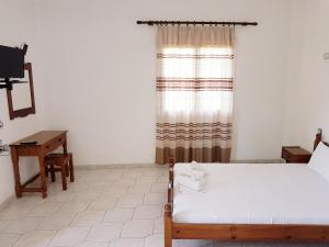 A bed or beds in a room at Amarandos Studios - Rooms & Apartments