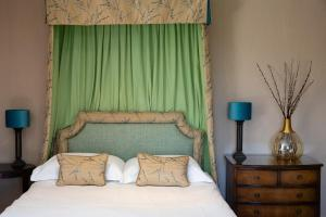 A bed or beds in a room at Burleigh Court Hotel