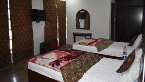 A bed or beds in a room at Hotel Shahzad International