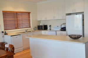 A kitchen or kitchenette at Arriva Holiday House - Bundalong