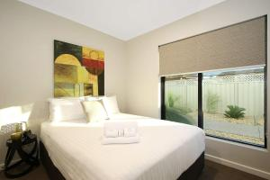 A bed or beds in a room at Lang Street Luxury Retreat - Mulwala