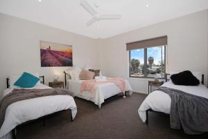 A bed or beds in a room at Mulwala Lakeside Townhouse #2