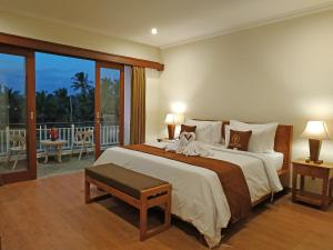 A bed or beds in a room at Paon Desa Ubud