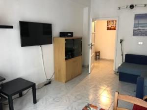 A television and/or entertainment center at HomeatHotel - Bilo Alcuino Apt.