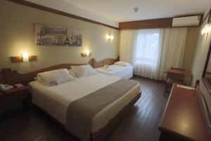 A bed or beds in a room at Vestena Hotel Canela