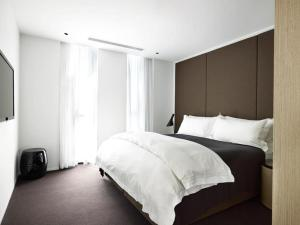 A bed or beds in a room at Burbury Hotel