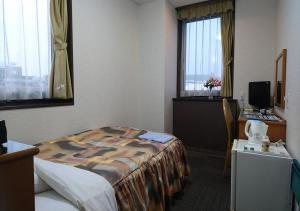 A bed or beds in a room at Terminal Hotel Matsuyama