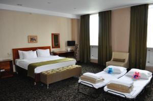 Кровать или кровати в номере Benefit Plaza Hotel