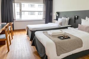 A bed or beds in a room at Slotshotellet Aalborg