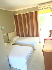 A bed or beds in a room at Hostal Alce