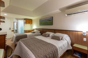 A bed or beds in a room at Bella Italia Hotel & Eventos